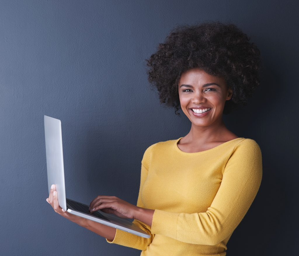 Studio shot of a young woman using her laptop against a grey background