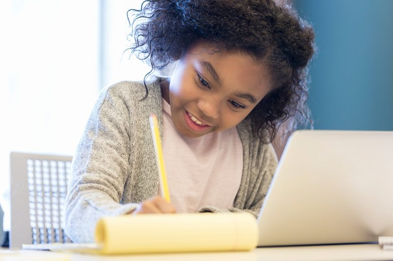 Confident young African American schoolgirl uses a laptop while studying. She is writing on a notepad.