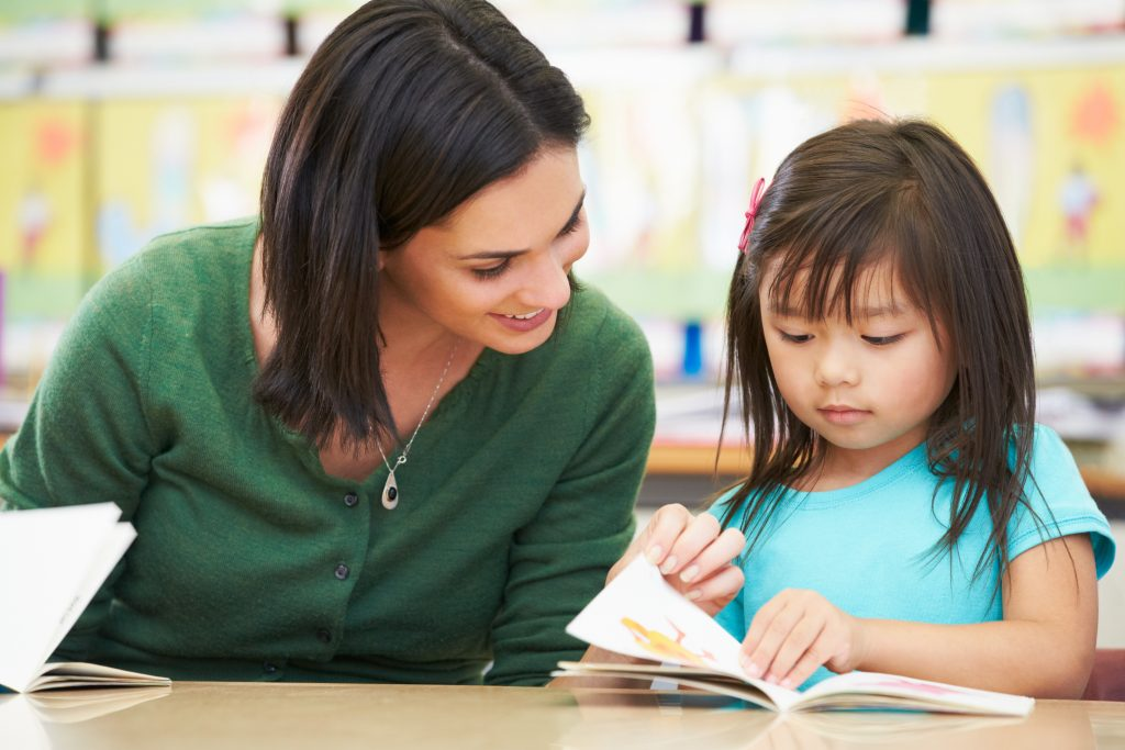 Elementary Pupil Reading With Teacher In Classroom Sitting Down