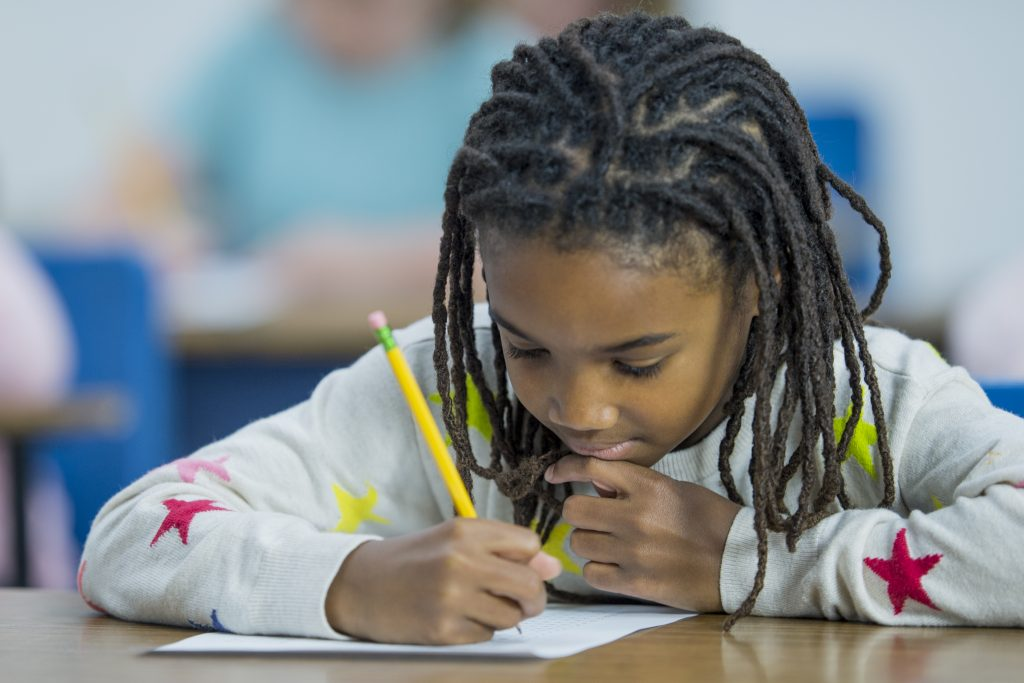 A multi-ethnic group of elementary school students are indoors in a school classroom. They are wearing casual clothing. A girl of African descent is writing a standardized test. She is topping to think.
